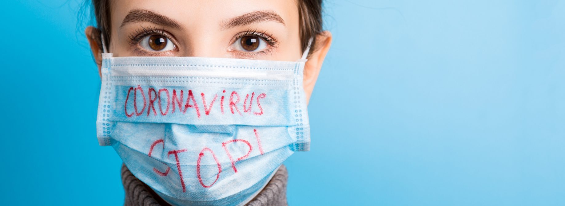 Portrait of a woman in medical mask with stop coronavirus text at blue background. Coronavirus concept. Respiratory protection